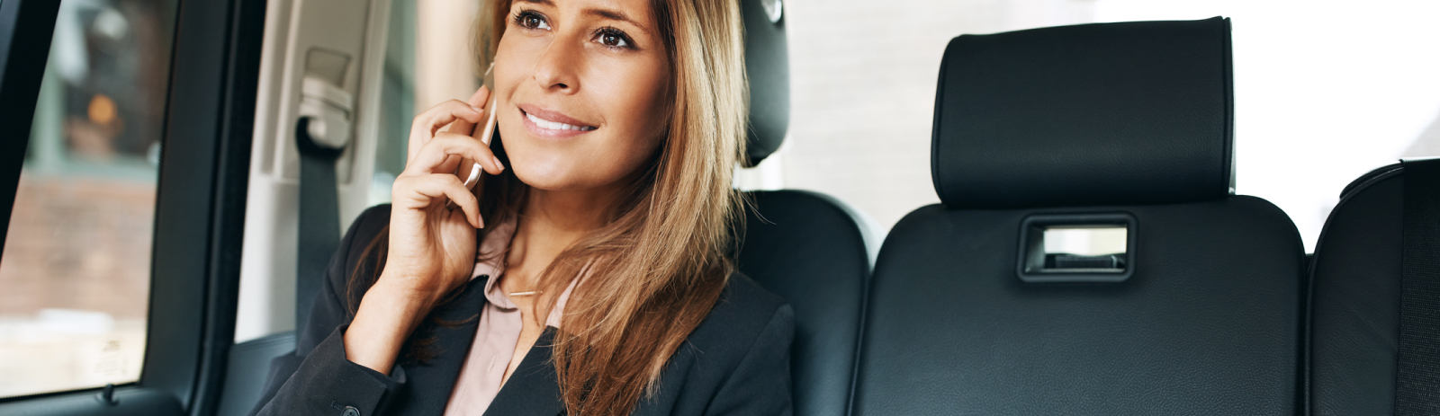 business woman in vehicle on her mobile phone